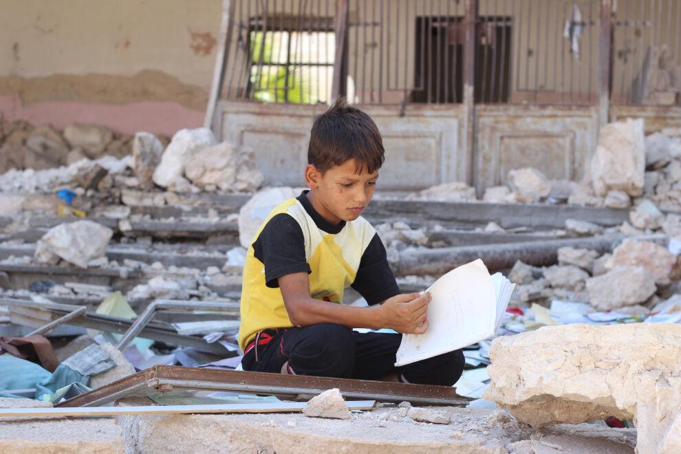 Aleppolainen poika asuu väliaikaiseksi suojaksi muutetussa koulussa. Sota on muuttanut Aleppon lasten elämän painajaiseksi. © UNICEF/UN029875/Al-Issa