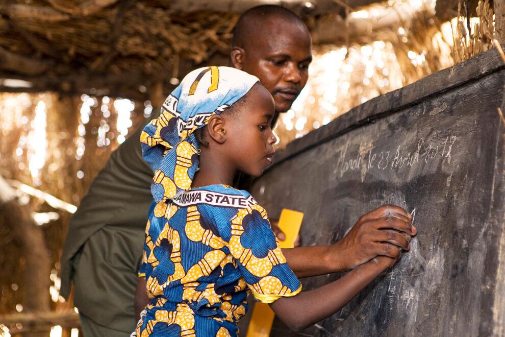 12-vuotias Chafiya saa tehtäväänsä apua opettajalta koulussaan Dan Goran kylässä Nigerissä. © UNICEF/UNI141585/Dicko