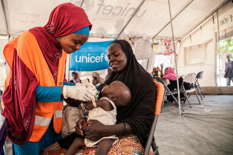 UNICEFin ravitsemusasiantuntija Aishat Abdullahi arvioi Umara Bukarin kuntoa. 7 kuukautinen Umara painoi vain 4,2 kiloa saapuessaan klinikalle Pohjois-Nigeriassa. Aliravittu lapsi sai apua klinikalla ja painaa nyt 5,1 kiloa. Kuva: UNICEF/Vittozzi