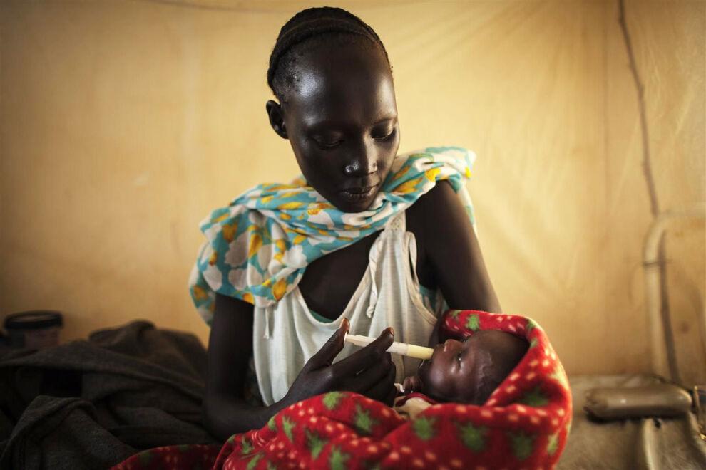 Eteläsudanilainen äiti syöttää aliravitsemuksesta kärsivälle lapselleen UNICEFin toimittamaa terapeuttista maitoa.