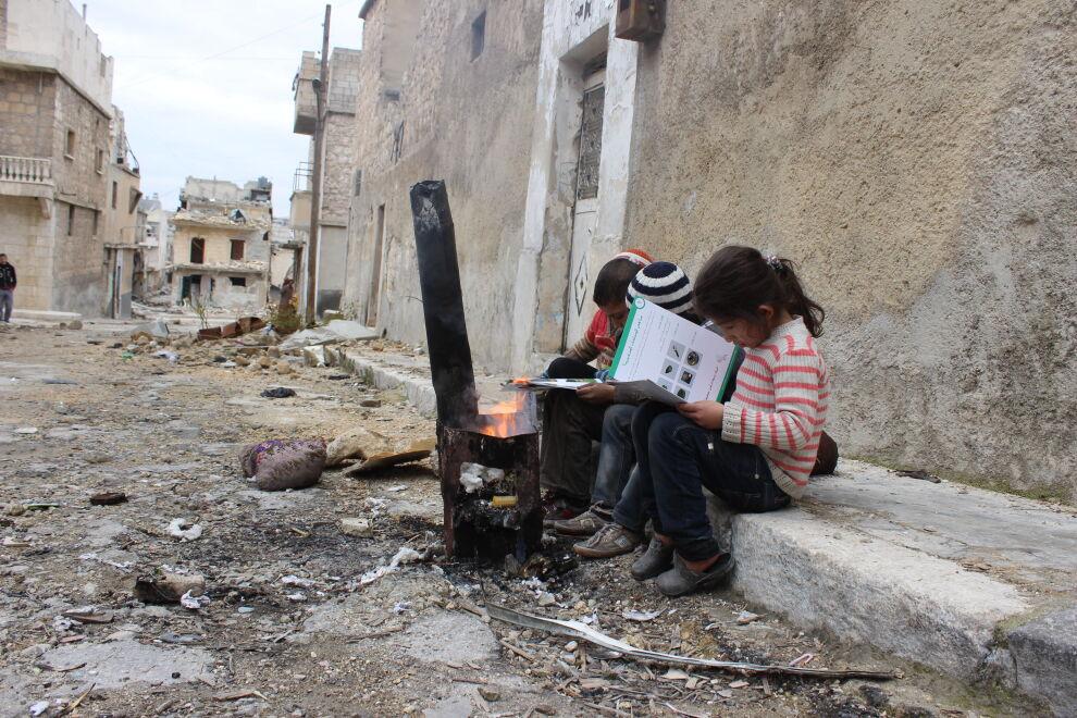 Syyrialaiset lapset opiskelevat vihkosesta, miltä räjähtämättömät ammukset näyttävät. UNICEFin tuella vapaaehtoiset työntekijät neuvovat lapsia varomaan ammuksia ja raportoimaan niistä oikealle taholle.  Kuva: ©UNICEF/ Syria 2016/ Khudr Al- Issa