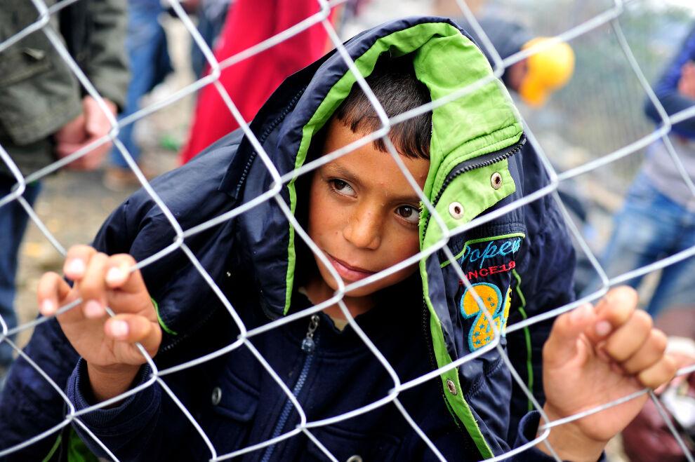 Nuori pakolaispoika katselee maailmaa aidan läpi Makedonian ja Kreikan rajalla.
