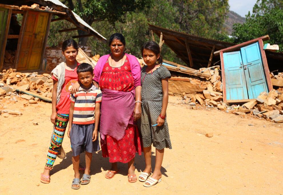 Shree Kalikan yläkoulun rehtori Rita Pyakhurel seisoo oppilaidensa Shanti Pyakhurelin, Sanjog Chalisen ja Samikshya Chalisen kanssa maanjäristyksessä tuhoutuneen koulun edessä Nuwakotissa Nepalissa. Ritan mukaan oppilaat kyselevät jatkuvasti, milloin he pääsevät takaisin kouluun. © UNICEF/Nepal 2015/Panday