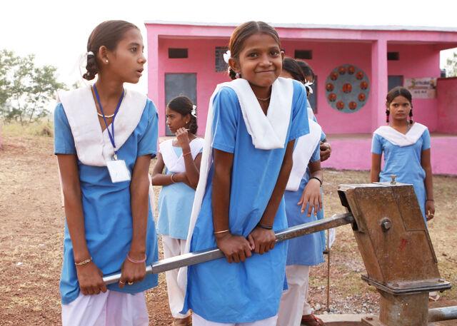 Tytöt pumppaavat vettä koulun pihalla Hilagnassa Madhya Pradeshin osavaltiossa. Koulu on mukana UNICEFin puhtaan veden ohjelmassa. © UNICEF/India2012/Haru