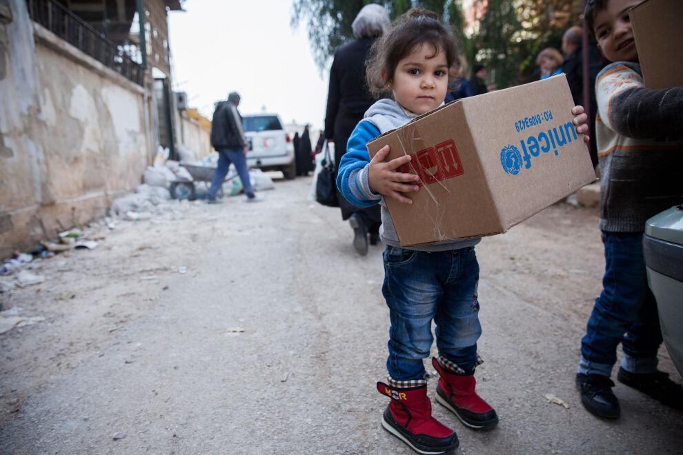 Syyrialainen maan sisäisessä paossa oleva lapsi sai talvivaatepaketin UNICEFilta al-Waerin kaupunginosassa Homsissa. © UNICEF/Syyria 2017/Martti Penttilä