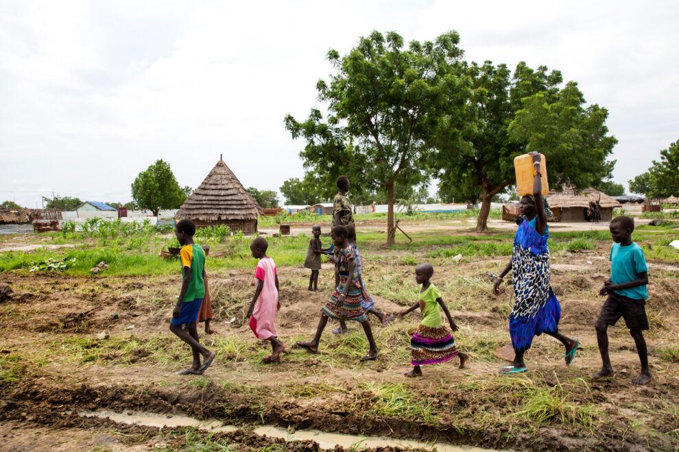 Eteläsudanilainen Angelina Nyakuma perheineen saa puhdasta vettä läheiselle koululle rakennetulta vesipumpulta Bentiun kaupungissa. Kolera, joka tarttuu likaisesta vedestä, on levinnyt Etelä-Sudanissa nopeammin kuin kertaakaan aiemmin maan historiassa. © UNICEF/UN075394/Kealey