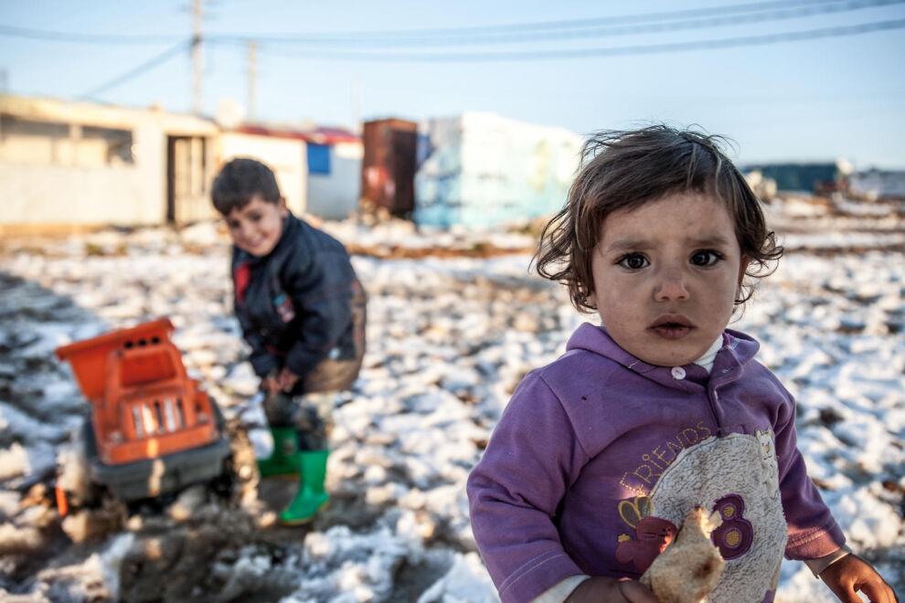 4-vuotias Ibrahim (taustalla) leikkii siskoineen lumessa Bar Ilyasin epävirallisella pakolaisleirillä Libanonissa. © UNICEF/UN0127909/Sanchez