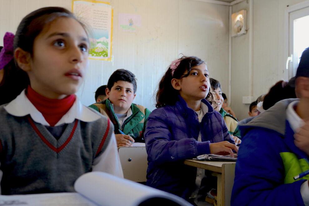 Syyrialaiset pakolaislapset opiskelevat talvitakit päällään Domizin pakolaisleirillä lähellä Dohukin kaupunkia Pohjois-Irakissa. UNICEF toimittaa kouluihin lämmityslaitteita. © UNICEF/UN0127684/Sparks