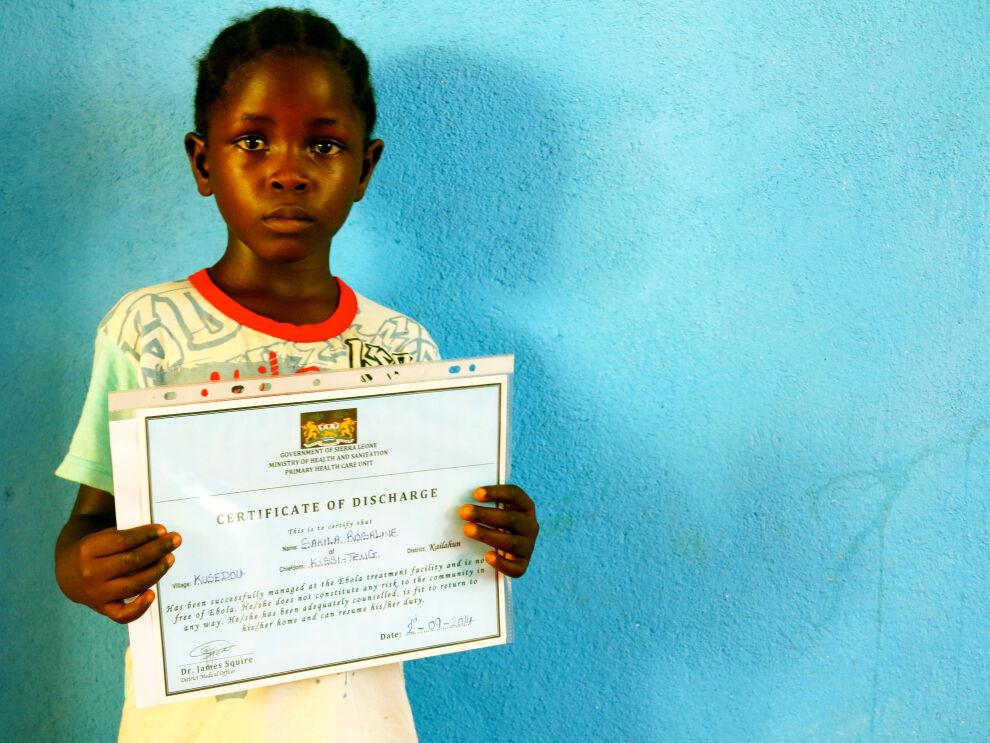Sierraleonelainen Rose, 5, menetti vanhempansa ja siskonsa Ebolalle. Hän sairastui myös itse, mutta parani. Nyt hän asuu veljensä kanssa UNICEFin tukemassa keskuksessa ja yrittää toipua kokemastaan. Rosella on kädessään todistus siitä, että hän ei kanna Ebola-virusta.