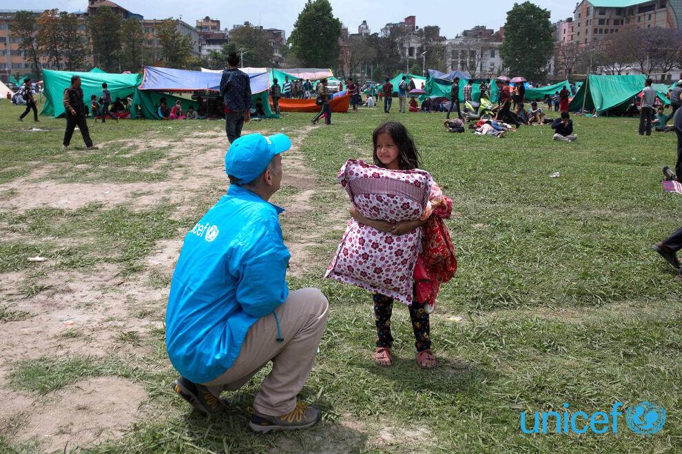 Kriisin keskelläkin pitää löytyä aikaa keskustella lasten kanssa ja lohduttaa heitä. Tämä tyttö etsi tyynynsä kanssa lepopaikkaa nurmikentällä Kathmandussa. © UNICEF/NYHQ2015-1007/Nybo