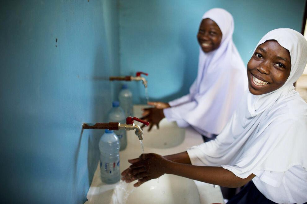 Koulunsa vesi- ja sanitaatiokerhossa olevat tansanialaiset tytöt näyttävät, miten he opettavat muita pesemään kätensä.