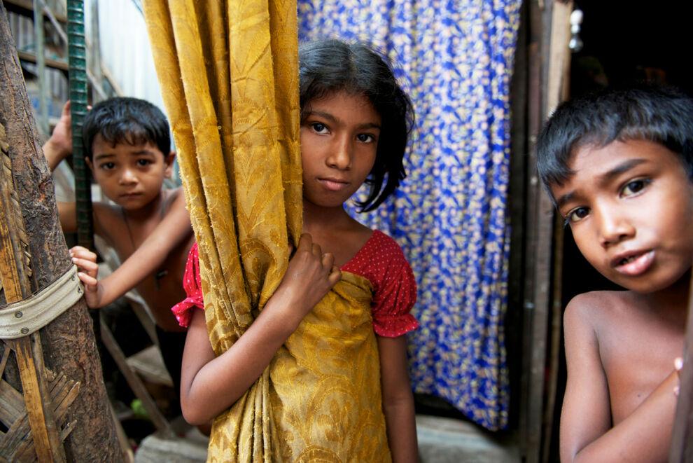 Laboni, 10, seisoo kotinsa oviaukolla Bangladeshin pääkaupungin Dhakan slummissa. Hän käy kolmatta luokkaa UNICEFin kumppanuusjärjestön koulua, joka on tarkoitettu äärimmäisestä köyhyydestä eläville lapsille. © UNICEF/UNI142699/Noorani
