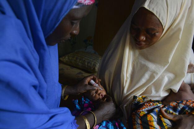 Assiye pitelee viiden päivän ikäisiä kaksospoikiaan Ubaidaa ja Shapaataa, kun terveystyöntekijä antaa heille poliorokotuksen Dambattassa, Nigeriassa. © UNICEF/NYHQ2015-0663/Rich