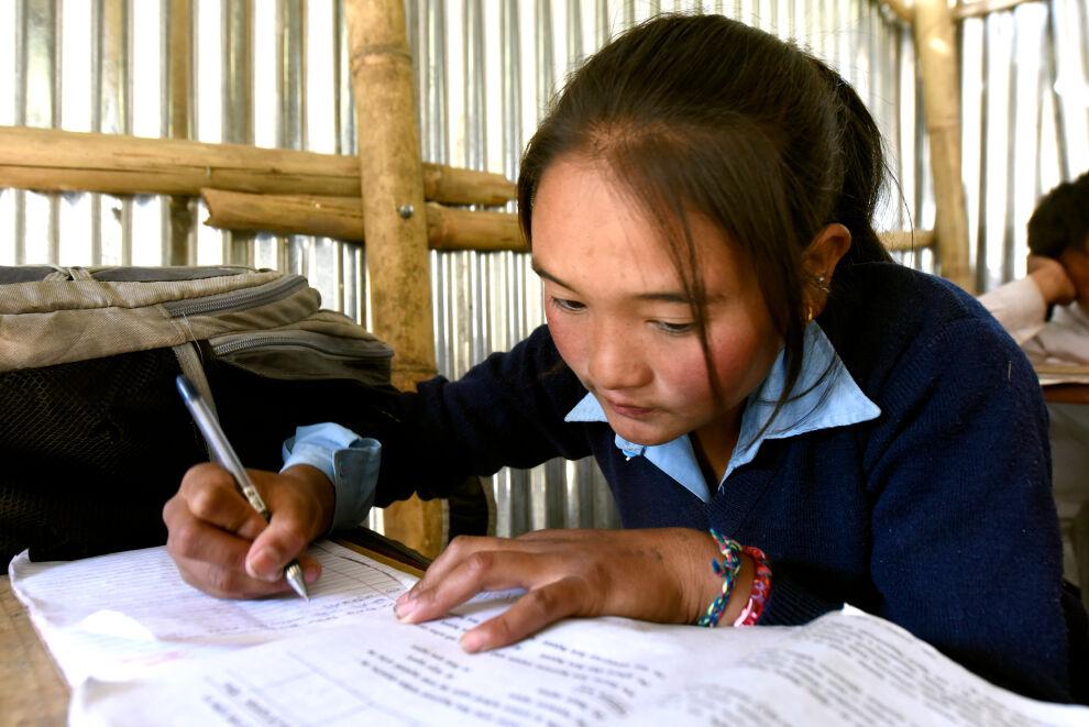 Kareena Tamang, 15, koulutöiden parissa Dhunchessa, Nepalissa. © UNICEF/UN04380/Karki