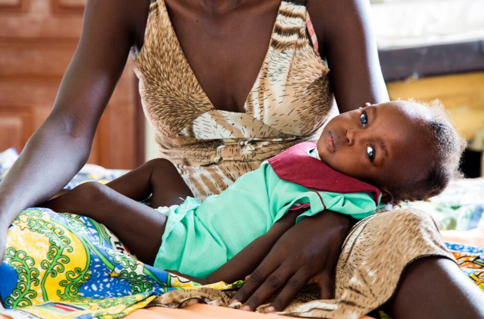 Vakavasta aliravitsemuksesta kärsivä puolitoistavuotias Elizabeth Kegi lepää äitinsä sylissä sairaalassa Etelä-Sudanin pääkaupungissa Jubassa. © UNICEF/UN053447/Gonzalez Farran