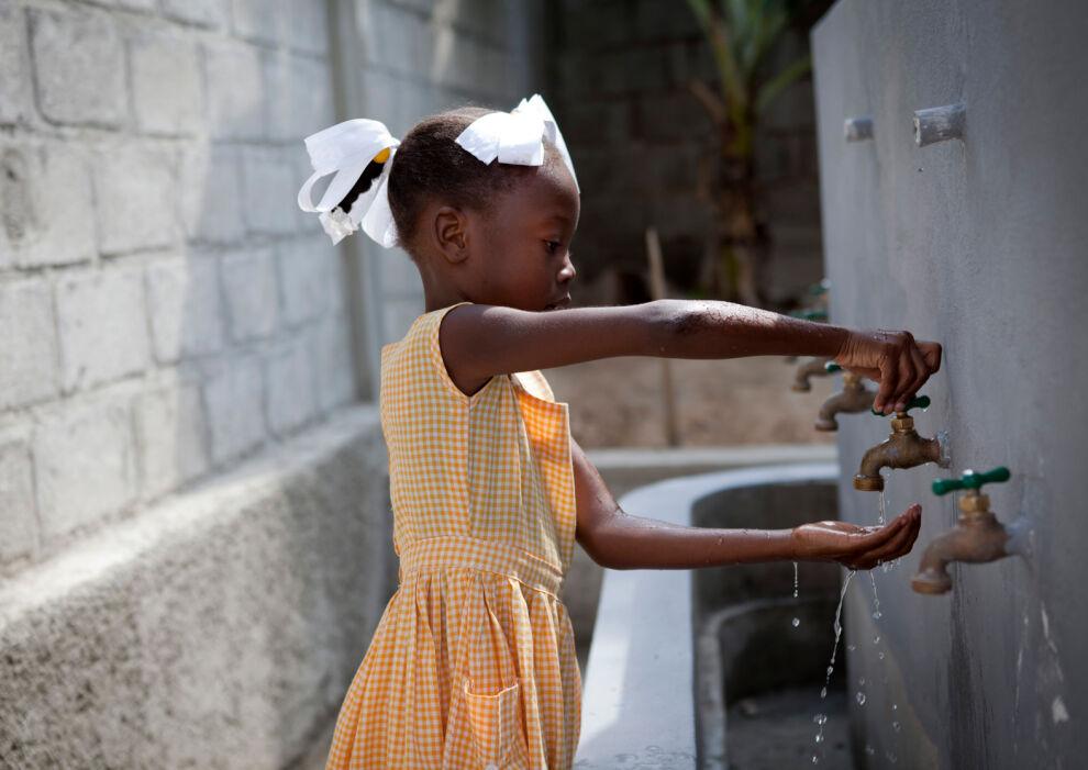 Tyttö pesee käsiään UNICEFin tuella rakennetussa käsienpesupisteessä koulussaan Port-au-Princessä, Haitilla. © UNICEF/UNI121139/Dormino