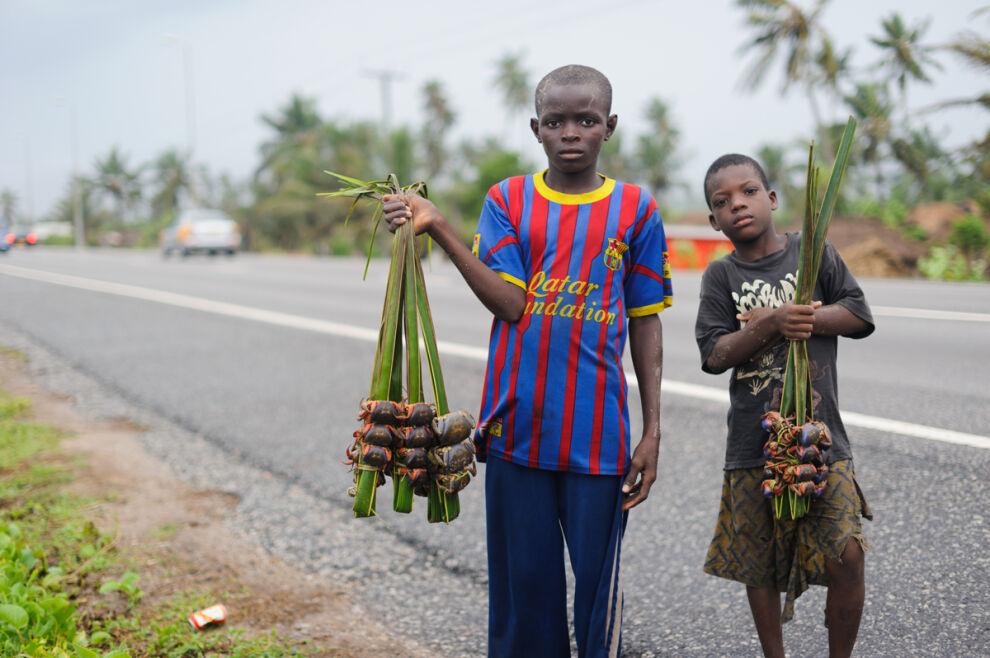 Ghanalaispojat Asiko ja Ishael myyvät rapuja tien varressa. Pojat eivät käy koulua, vaikka haluaisivat. © UNICEF/UNI198332/Quarmyne