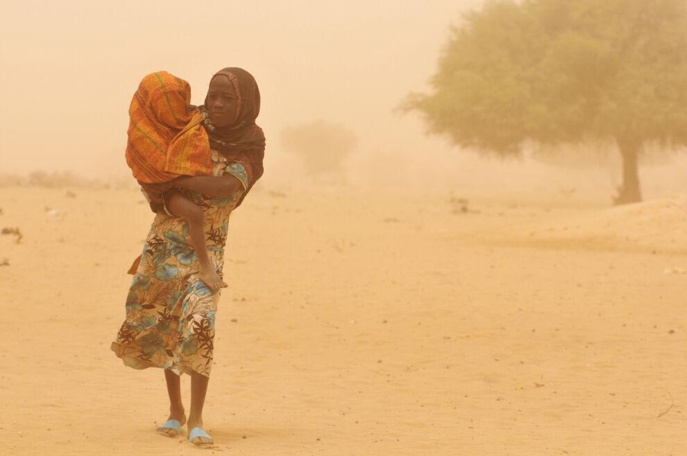 Tyttö kantaa pikkusisarustaan aliravitsemustarkastukseen keskellä rutikuivaa maisemaa Kanemin alueella Tšadissa. © UNICEF/UNI87634/Gangale