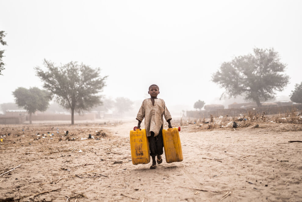 Poika kantaa vettä perheelleen pakolaisleirillä Nigerin Maradissa. Kuva: © UNICEF/UNI337865/Haro