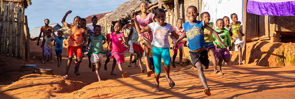 Iloiset lapset juoksevat kylällä.