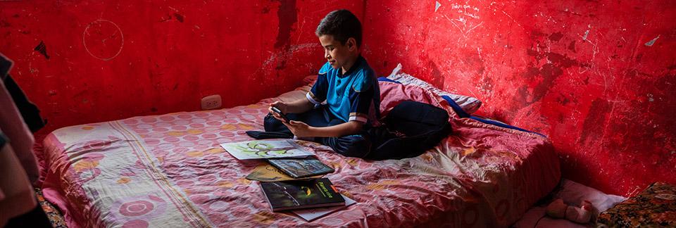 Koululainen lukee yksin koulukirjoja punaisessa huoneessa.