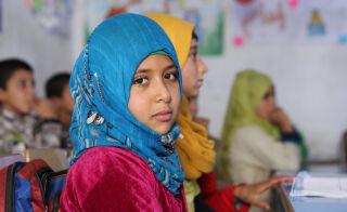 Siniseen huiviin ja viininpunaiseen puseroon pukeutunut tyttö katsoo vakavana kameraan. Taustalla näkyy luokkahuone ja muita lapsia.