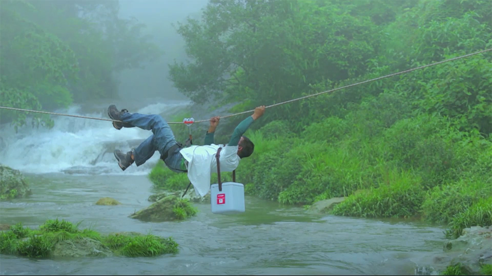 Rokotteiden kuljettaja ylittää joen köydessä roikkuen, rokotelaatikko selässään.