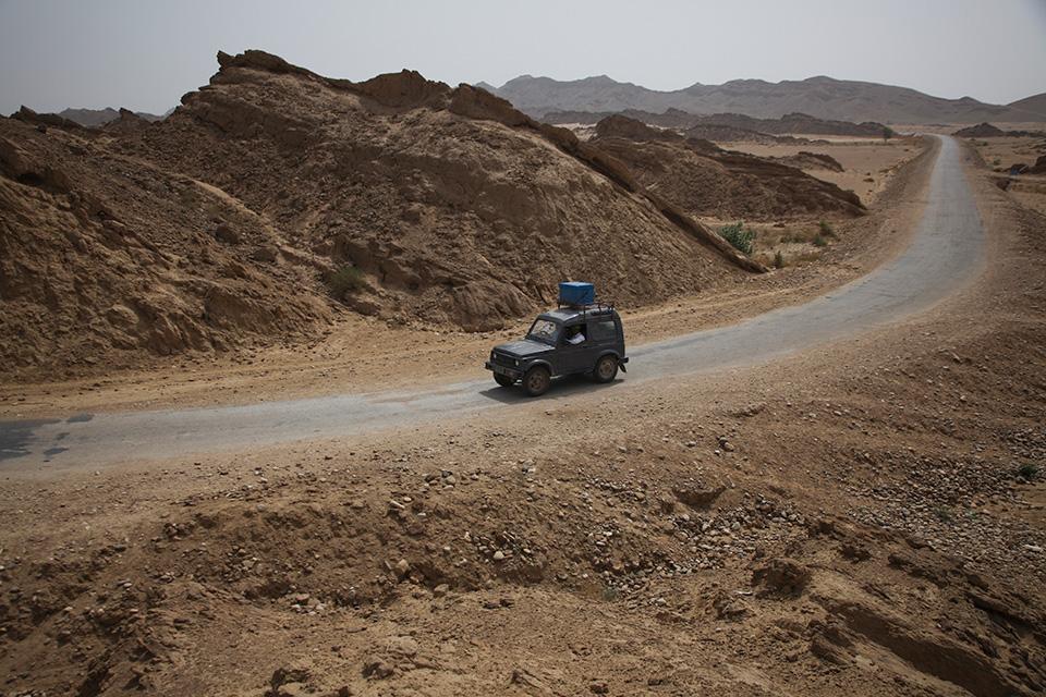 Maastoauto ajaa aavikolla sininen rokotelaukku katolla.