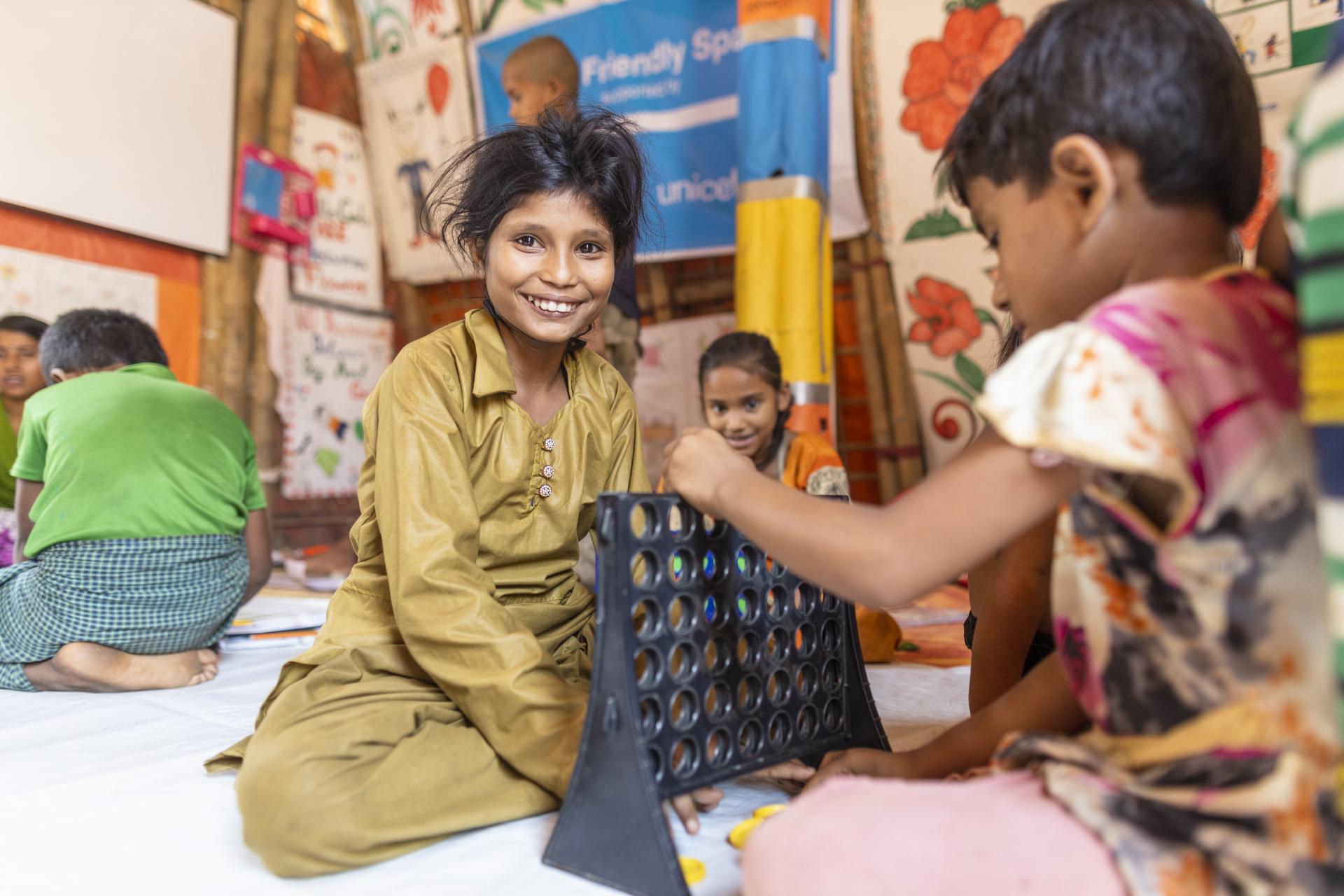 Kaksi lasta leikkii Cox's Bazaarin pakolaisleirillä UNICEFin tukemassa lapsiystävällisessä tilassa.