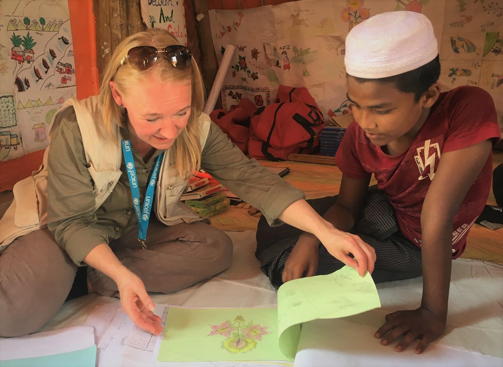 Kirsi Haru ja Manjur Ali katselevat lattialla istuen piirroksia.