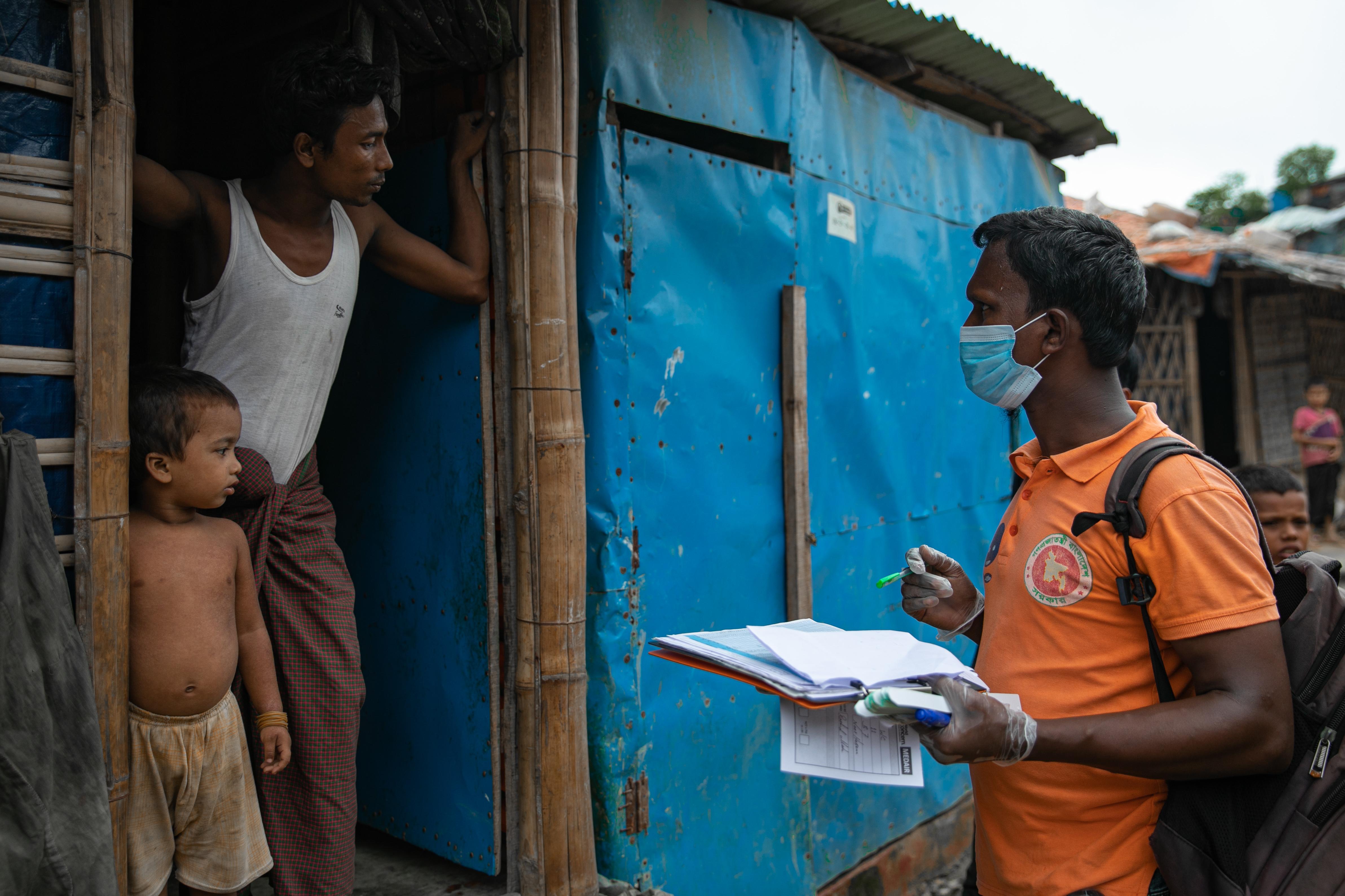 UNICEFin työntekijä keräämässä tietoja pakolaisten majan ovensuusssa.