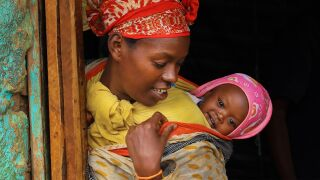 Äiti pitää vauvaa selässään. Vauva hymyilee ja kurkistaa selän takaa.