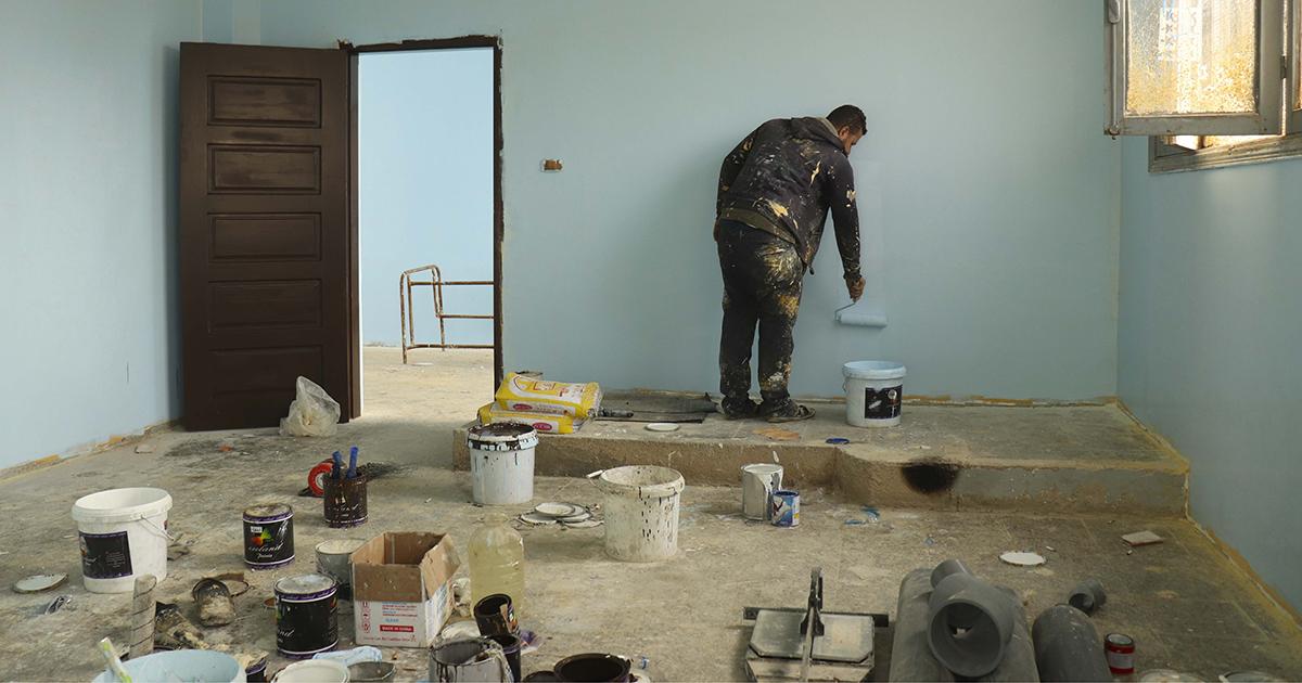 Mies maalaa luokkahuoneen seinää vaaleanvihreäksi.