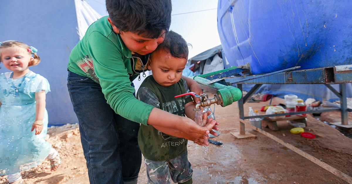 Lapset pesevät käsiään sinisen vesitynnyrin äärellä.