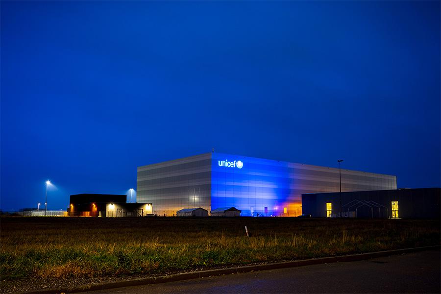 Illalla otettu valokuva, jossa UNICEFin varasto on valaistu siniseksi.