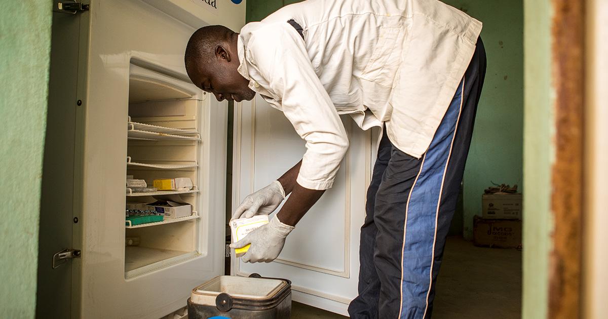 •Kobokotossoun terveysasemalla on UNICEFin tuella hankittu, aurinkoenergialla toimiva jääkaappi, jossa rokotteita voidaan säilyttää oikeassa lämpötilassa. Adama pakkaa rokotteet kylmälaukkuun ennen matkalle lähtöä.