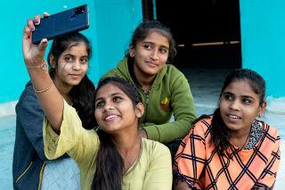 Neljä intialaistyttöä ottamassa selfie-kuvaa kännykällä.