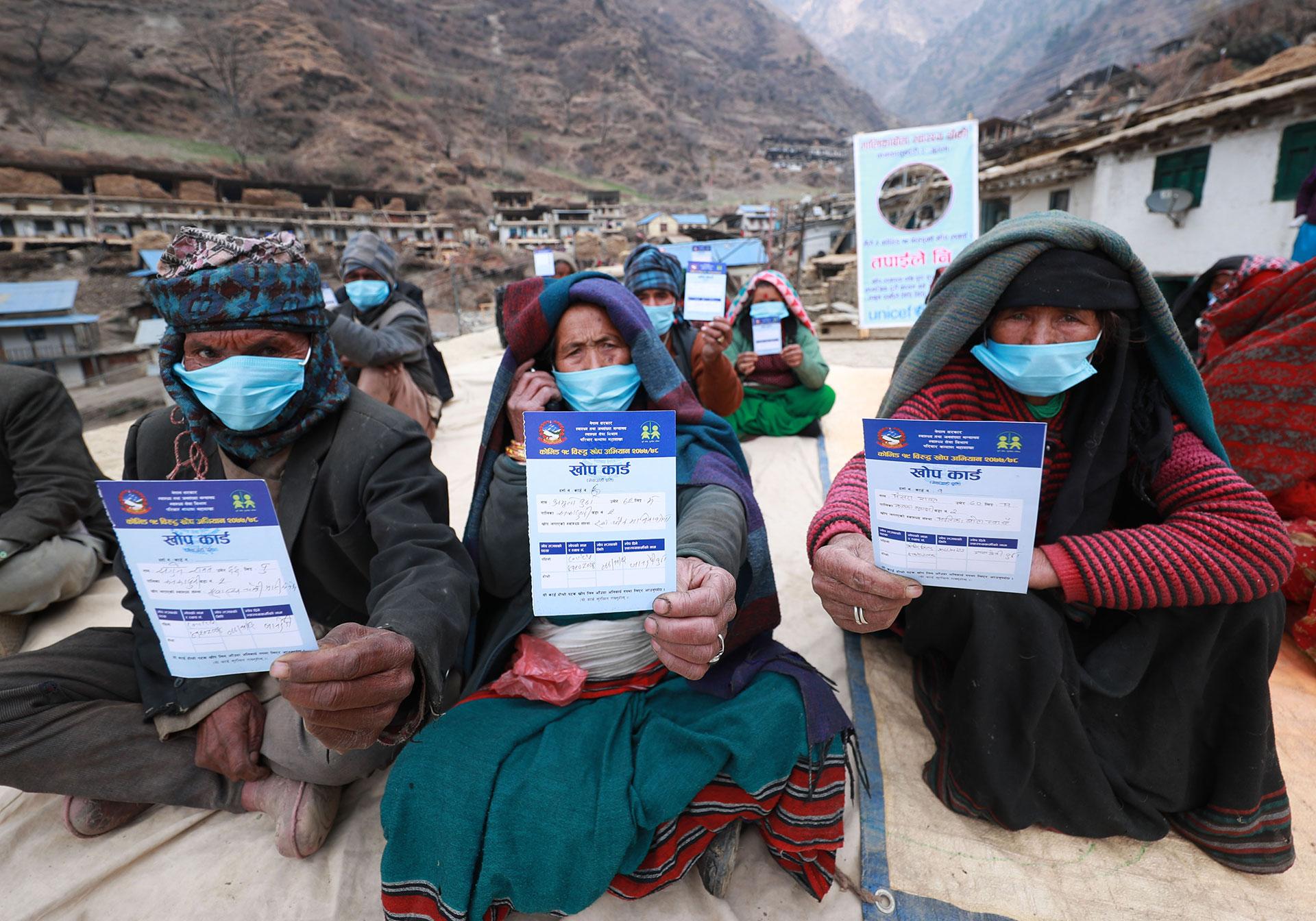 Kolme vanhusta esittelee rokotustodistuksia vuoristokylässä.