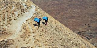 Kaksi ihmistä vaeltaa Nepalin vuoristomaisemassa siniset koronarokotereput selässään.