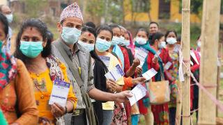 Värikkäästi pukeutuneet ihmiset jonottavat rokotukseen Nepalissa.