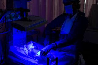 Vastasyntynyttä valvotaan hämärässä valossa teho-osastolla Dungapurin piirisairaalassa Intian Rajasthanissa.