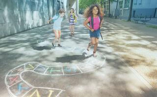 Kolme noin kymmenvuotiasta lasta leikki jalkakäytävälle.