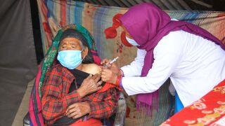 Vanhaa miestä rokotetaan.