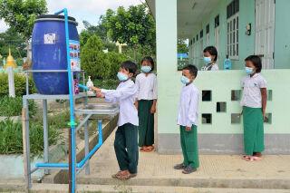 Maskeihin pukeutuneet lapset pesevät käsiä Myanmarissa.