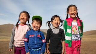 Neljä aasialaista lasta nauraa rivissä.