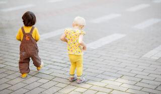 Kaksi leikki-ikäistä lasta astelee pois päin kamerasta kivetyllä aukiolla.