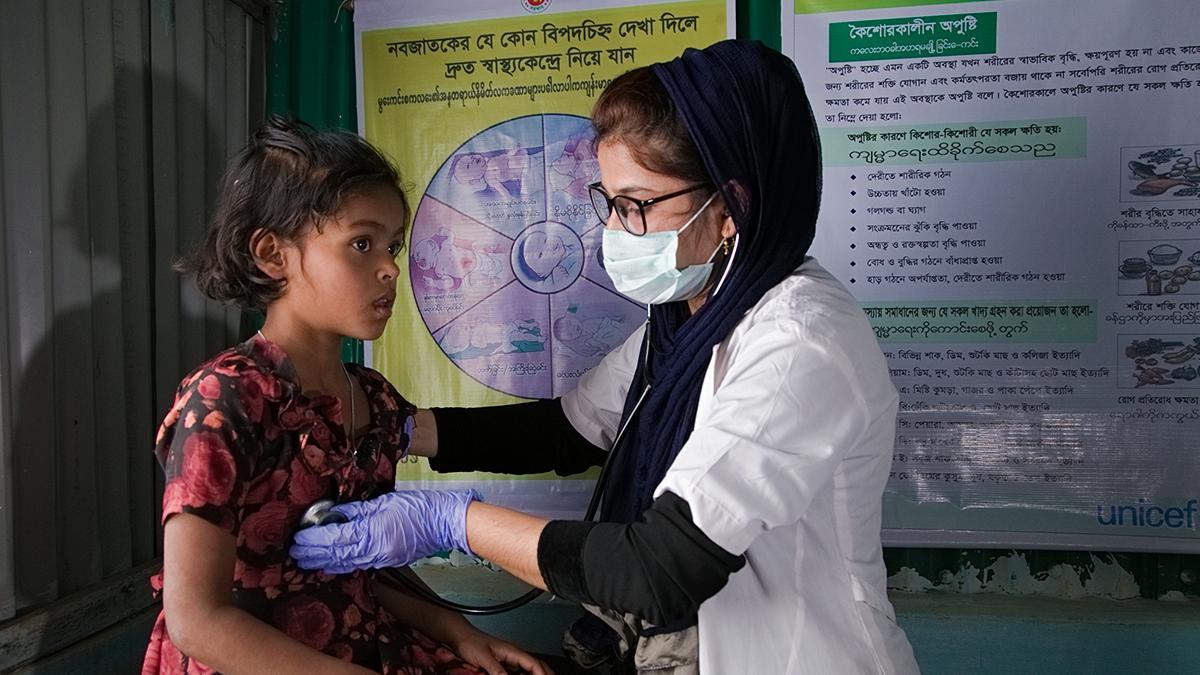 Terveydenhoitaja tarkastaa 7-vuotiaan tytön terveyden Cox Bazarin leirillä. Kuva: UNICEF/UNI337820/Bashir Ahmed Sujan