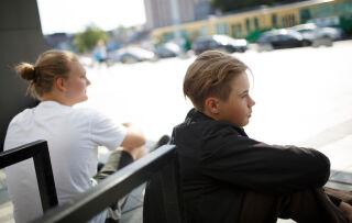 Kaksi teini-ikäistä poikaa istuu katumaisemassa selin kameraan. Taustalla näkyy raitiovaunu.
