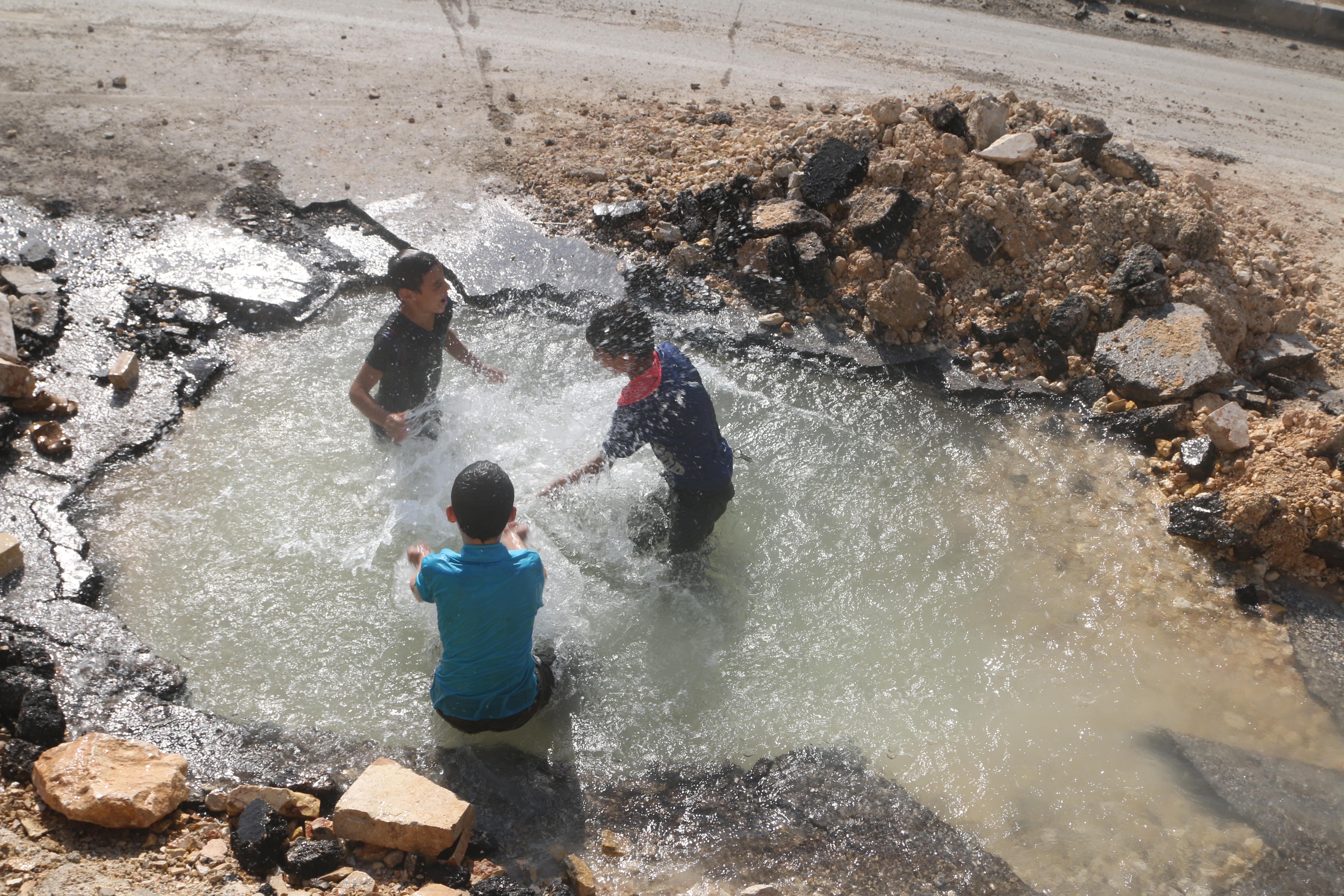 Lapset leikkivät pienessä vesilammessa.