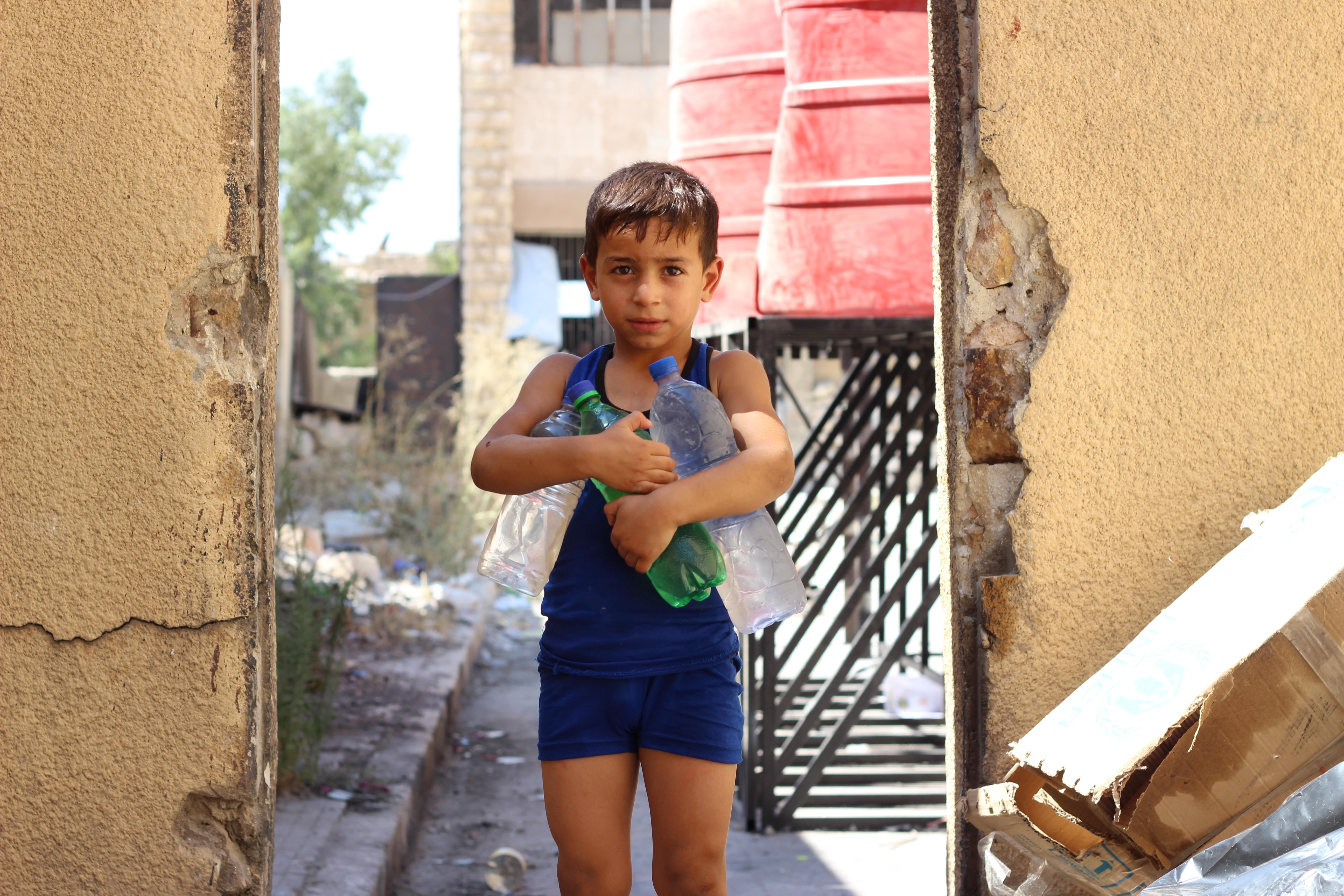 Lapsi kantaa kahta isoa vesipulloa.